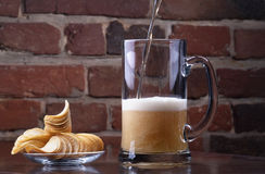 Glass of Fresh Beer and plate with chips Stock Image