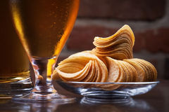 Glass of Fresh Beer and plate with chips. Background with glass of Fresh Beer and plate full of chips stock photo