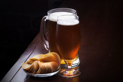 Glass of Fresh Beer and plate with chips Stock Photography