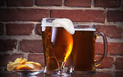 Glass of Fresh Beer and plate with chips Stock Images