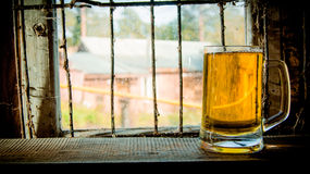 Glass of fresh beer on wooden shelf. On the background of an old window. Royalty Free Stock Photography