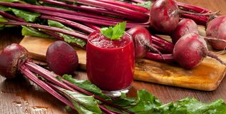 Glass of fresh beetroot juice with bets on wooden table. stock images