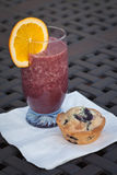 Glass of fresh blueberry smoothie next to blu. Glass of fresh blueberry orange smoothie with a homemade blueberry muffin Royalty Free Stock Photos