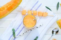 Glass of fresh cantaloupe smoothie on white wooden boards. Top V Royalty Free Stock Photo