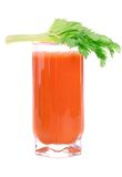 A glass of fresh carrot juice with celery leaves Stock Image