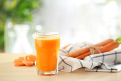 Glass of fresh carrot juice on light table. In the kitchen royalty free stock photo