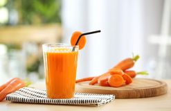 Glass of fresh carrot juice on light table. In the kitchen royalty free stock images