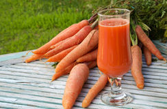 A glass of fresh carrot juice. On a wooden surface. Fresh carrots in the background. Free space for a text Royalty Free Stock Photography