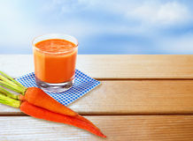 Glass of fresh carrot juice on wooden table with empty space. Royalty Free Stock Photo
