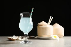 Glass with fresh coconut water on table. Against black background Royalty Free Stock Photography