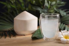Glass with fresh coconut water. On wooden table Stock Image