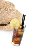 Glass of fresh coke with straw in front of summer hat, summer time Royalty Free Stock Photos