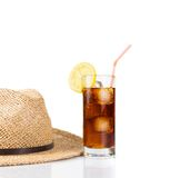 Glass of fresh coke with straw near summer hat, summer time. Glass of fresh coke with straw near summer hat on white background, summer time Royalty Free Stock Photography