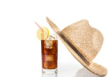 Glass of fresh coke with straw near summer hat on top, summer time Royalty Free Stock Photography
