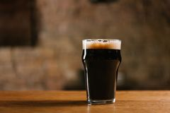 Glass of fresh cold dark beer on wooden table. In pub royalty free stock photography