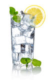 Glass of fresh cool water with lemon. Full glass of fresh cool transparent water with lemon and mint leaves Royalty Free Stock Photos