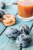 A glass of fresh Damson plum juice. On a blue rustic wooden table close-up Royalty Free Stock Photo