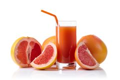 Glass of fresh grapefruit juice and cut fruits white background. Glass of fresh grapefruit juice and cut fruits isolated on white background Stock Images