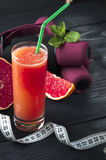 Glass of fresh grapefruit juice, measuring tape and dumbbells Royalty Free Stock Image