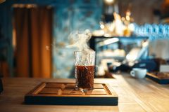 Glass of fresh hot black coffee, side view. Glass of fresh hot black coffee stands on wooden counter in espresso cafe, side view, cafeteria interior on royalty free stock image