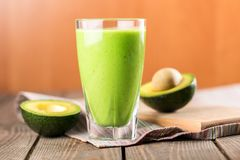 Glass of fresh juice and avocado halves on wooden. Glass fresh juice avocado halves healthy lifestyle low calorie Royalty Free Stock Photography