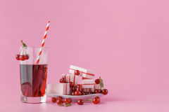 Glass of fresh juice with cherries on bright background Stock Images