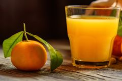 Glass of fresh juice and mandarins on table. Glass of healthy fresh juice of mandarins or tangerine on rustic wooden background. Selective focus Stock Images