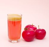 Glass with fresh  juice and red apples. Fresh neat juice and three red apples on pink background Royalty Free Stock Photography