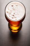 Lager beer on table. Glass of fresh lager beer on black table Royalty Free Stock Image