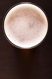 Lager beer on table. Glass of fresh lager beer on black table Royalty Free Stock Images