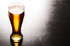 Lager beer on table. Glass of fresh lager beer on black table Royalty Free Stock Photography
