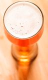 Lager beer on table. Glass of fresh lager beer on wooden table Royalty Free Stock Photo