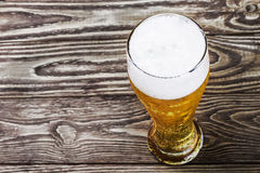Glass of fresh lager beer on a wooden table. Focus on Foam Stock Photo