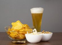 Glass of fresh light beer and snack Stock Images