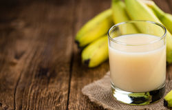 Glass with fresh made Banana juice. (selective focus) on an old wooden table Royalty Free Stock Photo