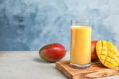 Glass of fresh mango drink and fruits on table against color background. Space for text royalty free stock images