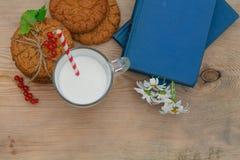 Glass of fresh milk with fresh raspberries ripe for breakfast on. Glass of fresh milk with fresh raspberries ripe for breakfast and books on a wooden background Stock Photos