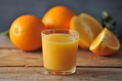 Glass with fresh orange juice on the background of whole oranges. On a wooden rustic background Royalty Free Stock Photography