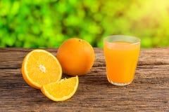 Glass of Fresh Orange Juice on grunge wooden table. Glass of Fresh Orange Juice and full, Half Orange t on grunge wooden table Stock Image