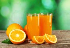 Glass of fresh orange juice on grey wooden background. Stock Images
