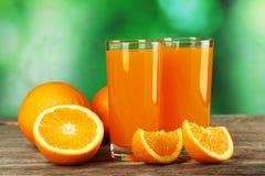Glass of fresh orange juice on grey wooden background. Stock Image