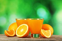 Glass of fresh orange juice on grey wooden background. Royalty Free Stock Images