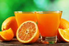 Glass of fresh orange juice on grey wooden background. Royalty Free Stock Photos