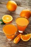 Glass of fresh orange juice on a grey wooden background Stock Photos