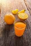 Glass of Fresh Orange Juice on grunge wooden table. Glass of Fresh Orange Juice and full, Half crescent Orange Fruit on grunge wooden table Stock Photography