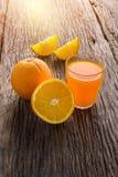 Glass of Fresh Orange Juice on grunge wooden table. Glass of Fresh Orange Juice and full, Half crescent Orange Fruit on grunge wooden table Royalty Free Stock Photo