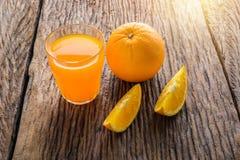 Glass of Fresh Orange Juice on grunge wooden table. Glass of Fresh Orange Juice and full, Half crescent Orange Fruit on grunge wooden table Stock Photo