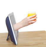 Glass with fresh orange juice in hand leans out TV Royalty Free Stock Photos