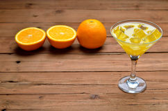 A glass of fresh orange juice with ice cubes on brown wooden bac Royalty Free Stock Photo