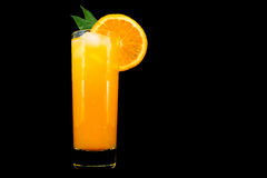 Glass of fresh orange juice with ice and a slice of orange with leaves isolated on black background Stock Images